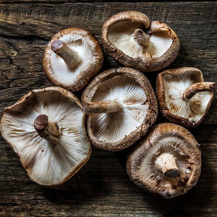 Beautiful Shiitake mushrooms, organically arranged on a rustic wooden background.