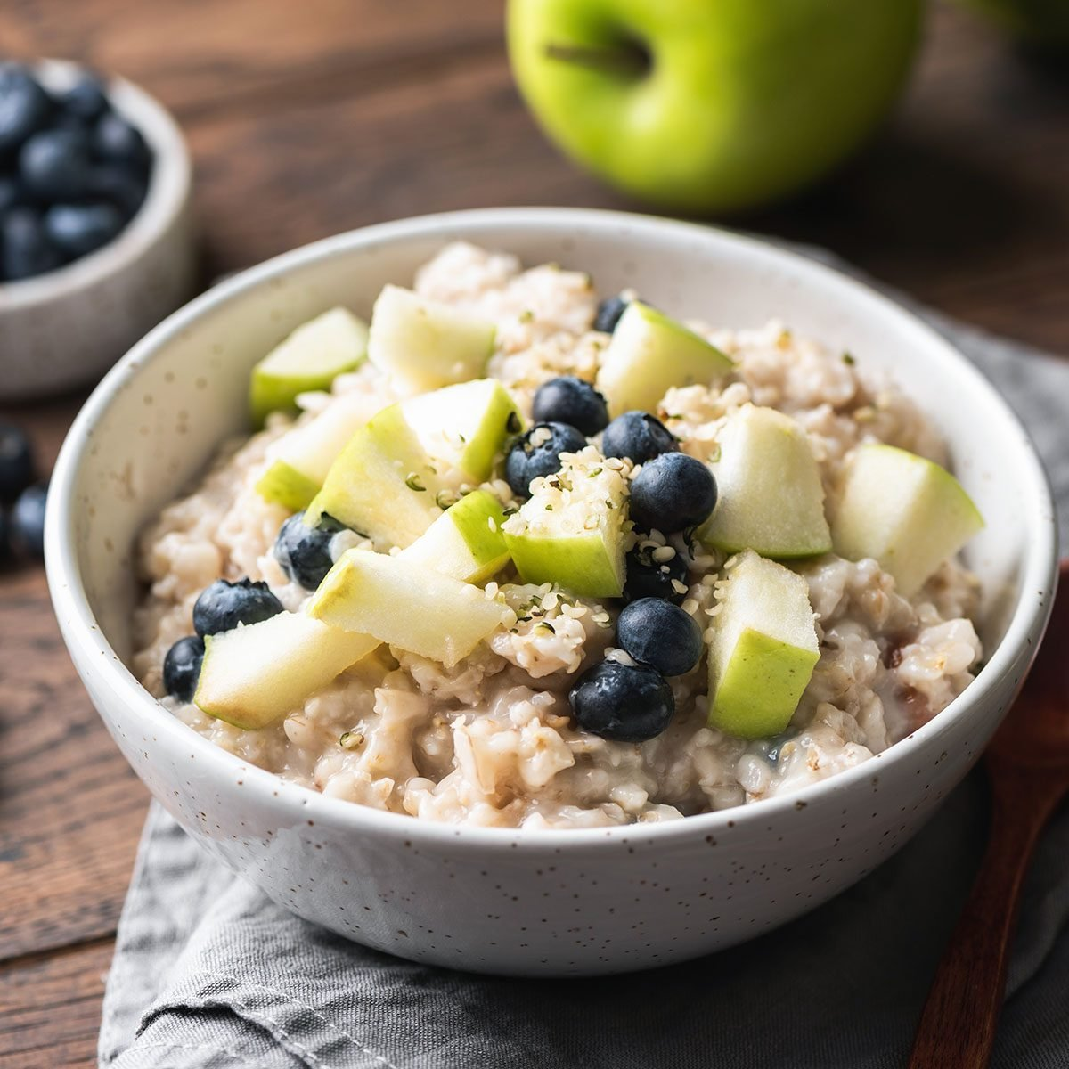 Oatmeal porridge with green apple, hemp seeds and blueberries