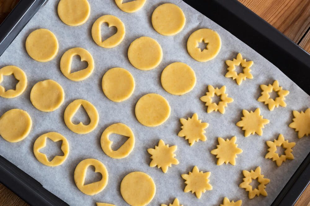 Preparation of Linzer Christmas cookies - cut out shapes on a baking sheet