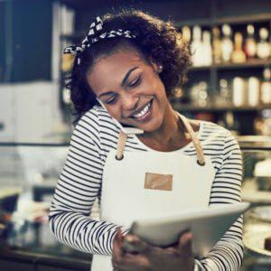 Smiling young black entrepreneur standing at the counter of her cafe talking on a cellphone and using a tablet