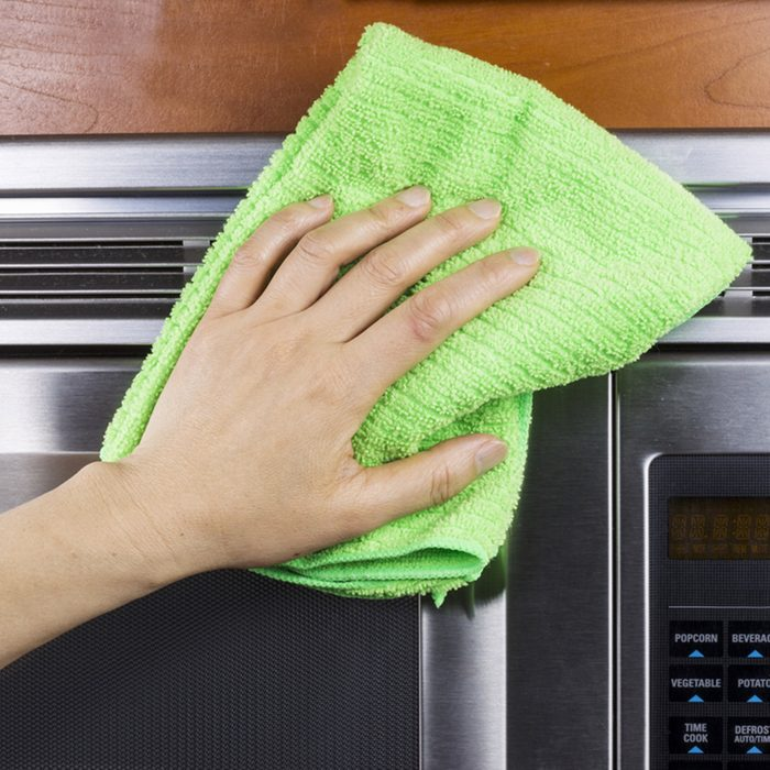 Hand with microfiber rag cleaning vents of microwave oven; Shutterstock ID 121364071; Job (TFH, TOH, RD, BNB, CWM, CM): Taste of Home