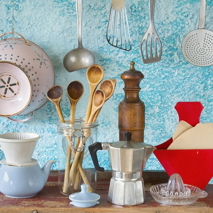 various vintage kitchen utensils,against blue wall