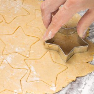 Making gingerbread christmas cookies with metal cutter. Ginger dough and flour