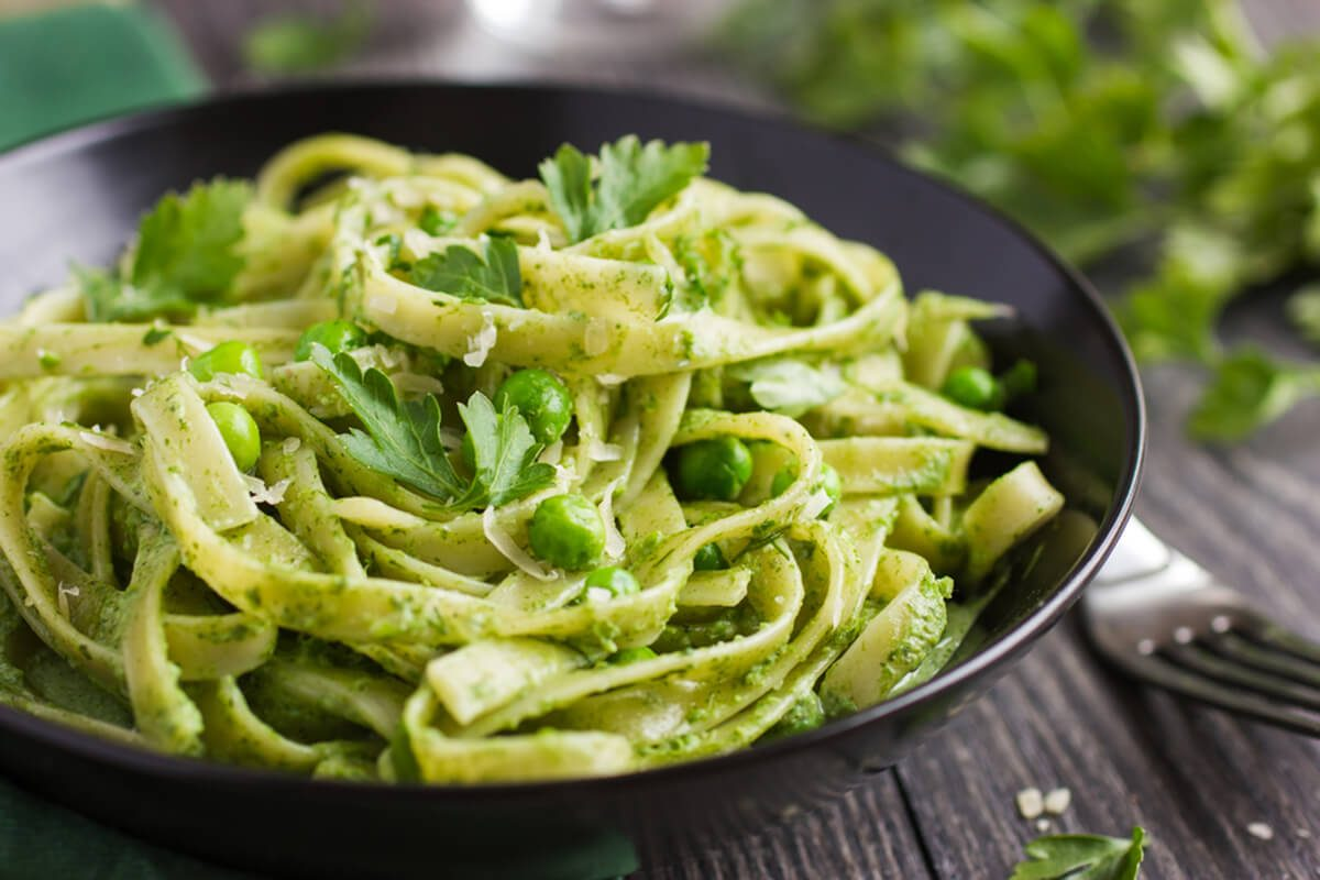Tagliatelle pasta with spinach and green peas pesto, selective focus