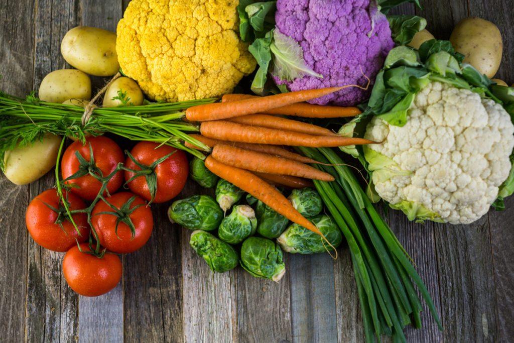 Fresh organic vegetable in season on old farm table.