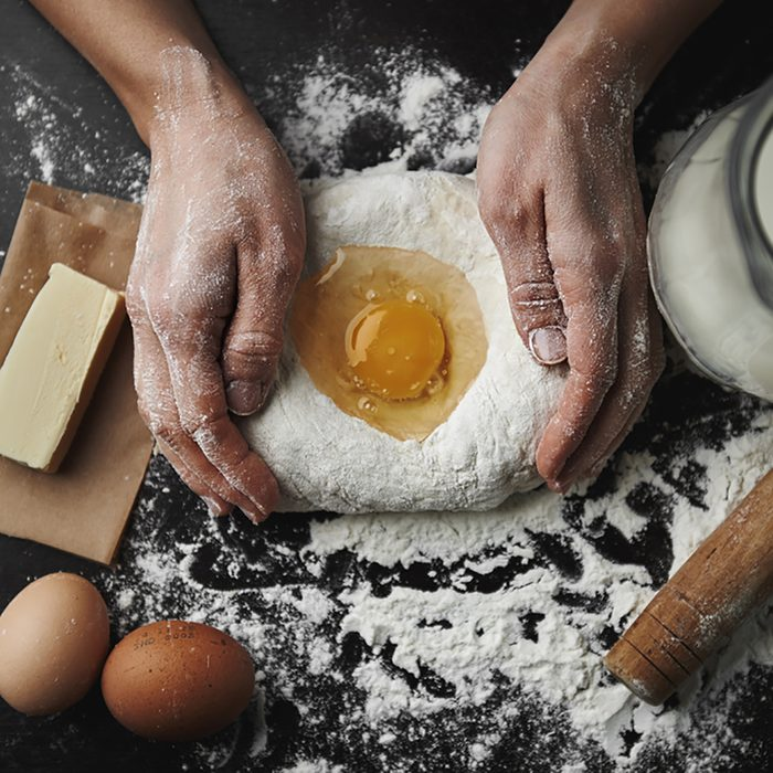 Professional female baker cooking dough with eggs, butter and milk for Christmas cookies. ; Shutterstock ID 340582067; Job (TFH, TOH, RD, BNB, CWM, CM): Taste of Home