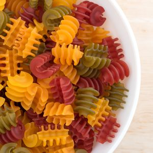 Top close view of a portion of gluten free corn vegetable radiatore pasta in a white bowl on a wood table top illuminated with natural light.