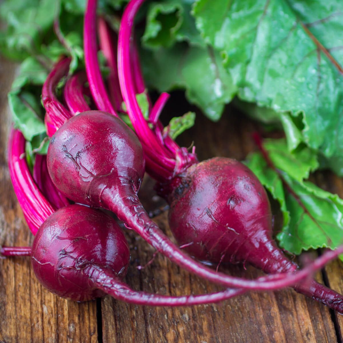 Organic red beets with green leaves on an old wooden table. Rustic style