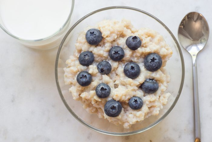 Bowl of oatmeal porridge with blueberry on marble table, with glass of milk, hot and healthy breakfast every day, diet food