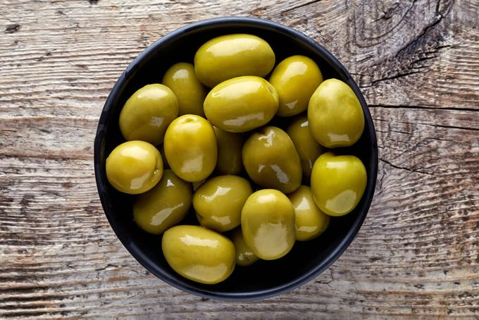 Bowl of pickled olives on wooden background, top view