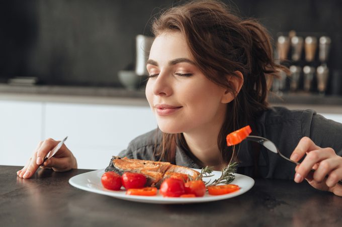 Image of pretty young woman sitting in kitchen while eating and smells fish and tomatoes. Eyes closed