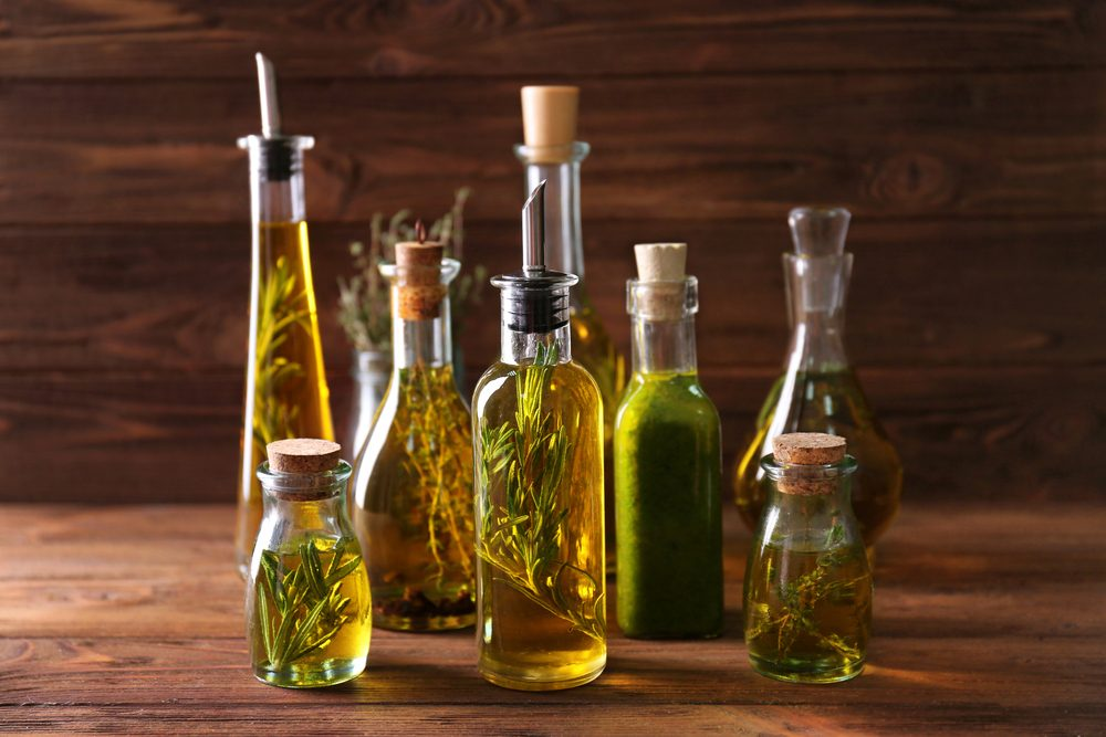 Composition of bottles with oil on wooden background. Keto diet-friendly oils.