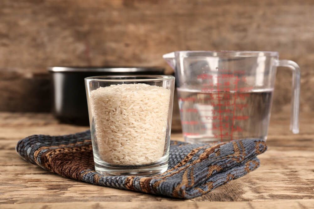 Glass of rice and measuring jug with water on wooden table