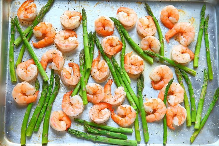 Sheet pan dinner of shrimp and asparagus with olive oil and black pepper.