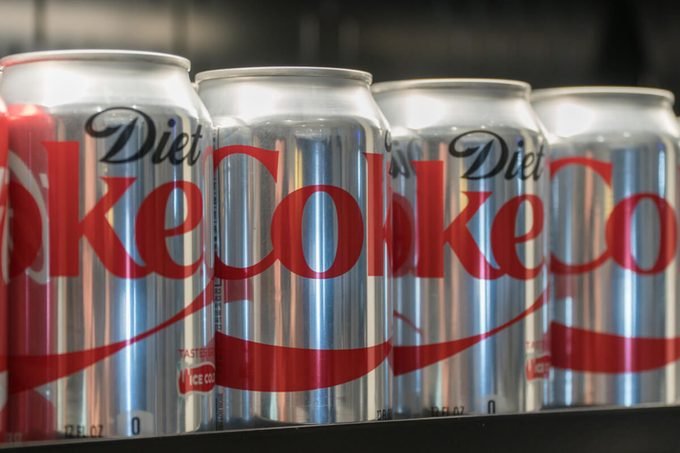 Diet Coke cans on store shelf for customer purchase.