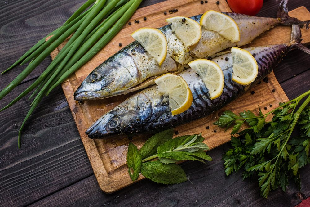 Fish dish cooking with various ingredients. Raw mackerel with lemon, garlic, herbs and spices on cutting board, top view. Healthy food or diet nutrition concept