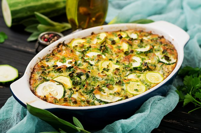 Zucchini casserole with eggs, milk, cheese and greens herbs