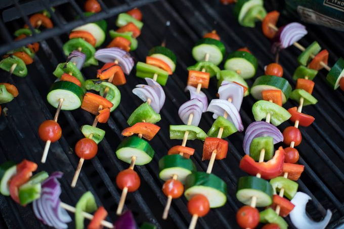 Overhead top down view colorful raw vegetarian appetizer vegetable kabab with bell peppers and red onion pieces on bamboo skewer with cucumber slices and impaled cherry tomato on barbecue gas grill