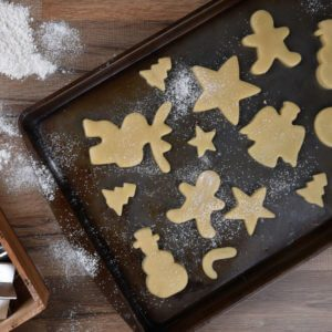 Top view of a baking sheet with a holiday shaped sugar cookies, with a rolling pin and wood box of cookie cutters on the side
