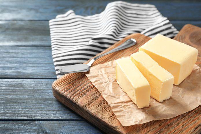 Cut block of butter on wooden board