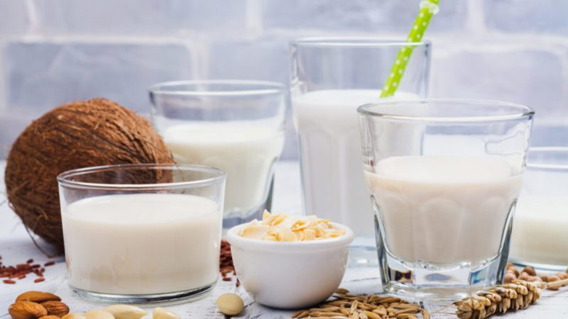 Assortment of non dairy vegan milk and ingredients on white wooden background.