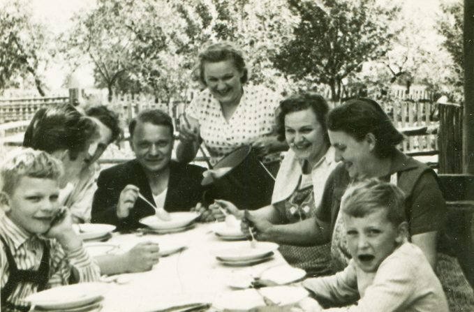 Vintage photo of happy family dining outdoor (fifties);