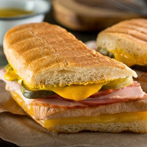 An authentic cuban sandwich on pressed medianoche bread with pork, ham, cheese, pickle, and mustard