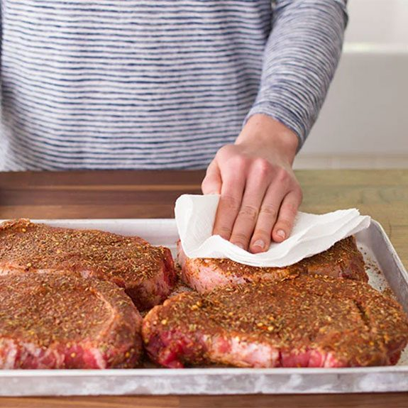 Patting seasoned raw steaks with a paper towel