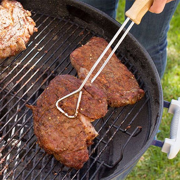 Picking up steak on grill with tongs
