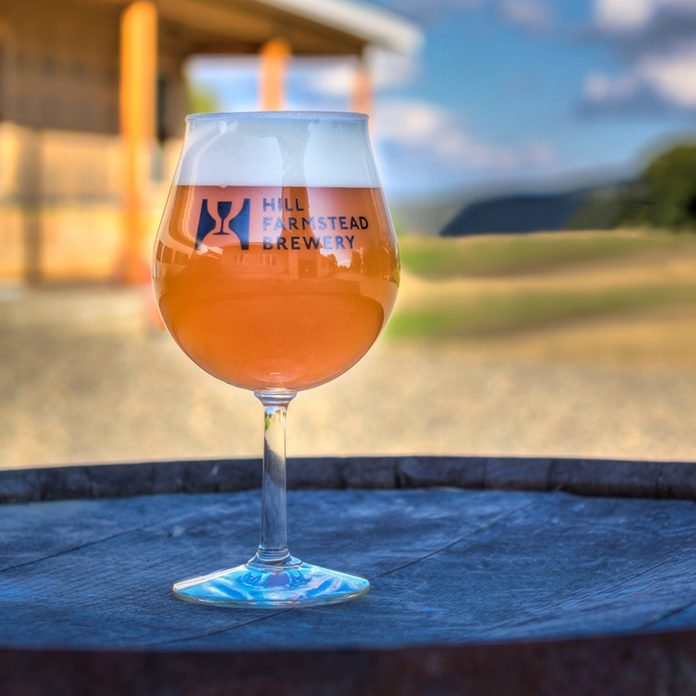 Hill Farmstead beer glass on wooden barrel outside
