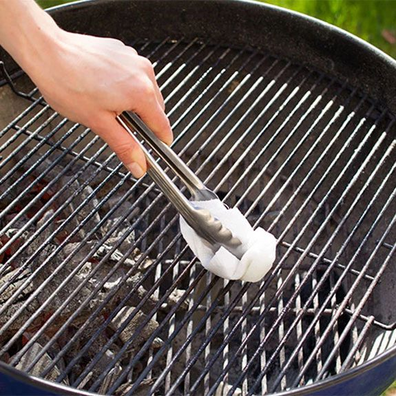 Wiping grill with paper towel in tongs