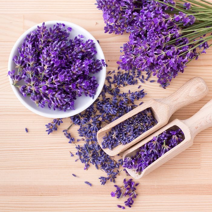 Top view of a bowl and wooden spoons with dried and fresh lavender flowers and a bouquet of lavender on a wooden background ; Shutterstock ID 669397450; Job (TFH, TOH, RD, BNB, CWM, CM): Taste of Home