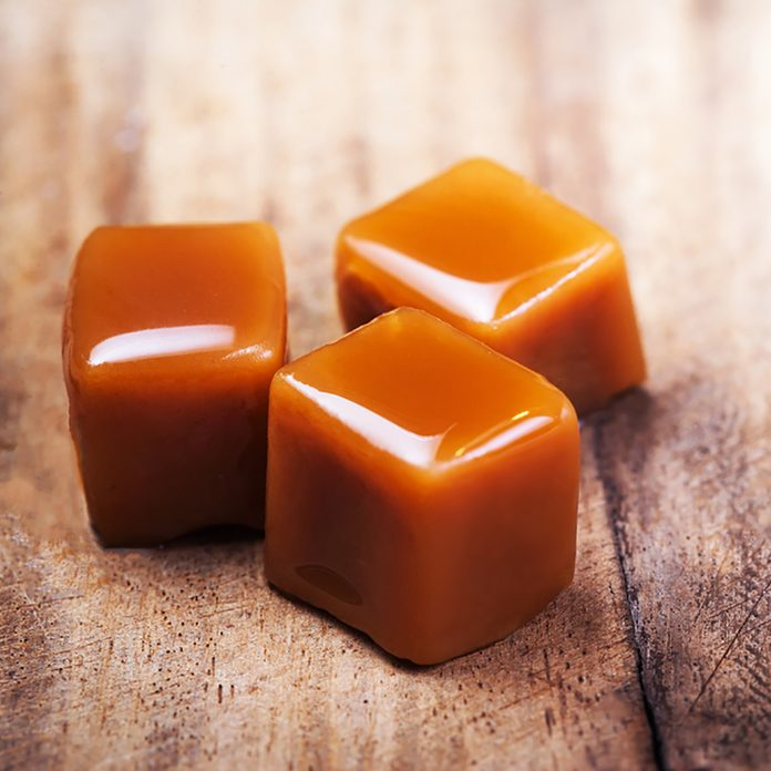 Homemade salted caramel pieces on wooden background. Golden Butterscotch toffee candy caramels with copyspace.; Shutterstock ID 754713457; Job (TFH, TOH, RD, BNB, CWM, CM): Taste of Home