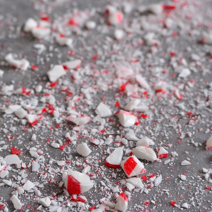 Crushed peppermint candy cane bits sprinkled on wax paper background