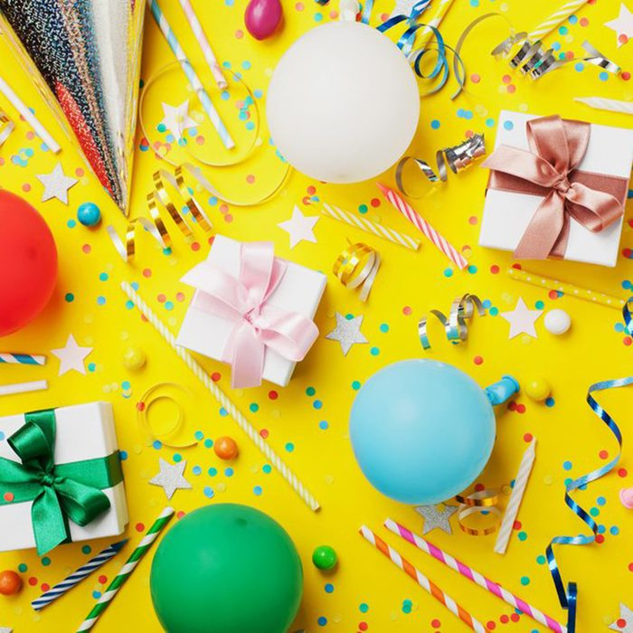 Birthday party background with balloon, gift, confetti, carnival cap, star, candy and streamer. Flat lay style. Colorful children greeting card.; Shutterstock ID 704524666; Job (TFH, TOH, RD, BNB, CWM, CM): TOH