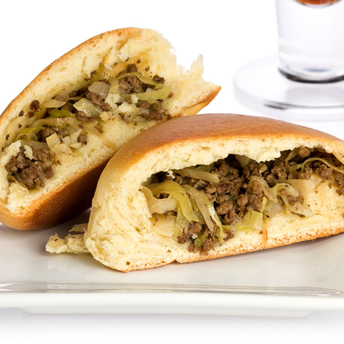 Single sliced bierock with seasoned ground beef, cabbage, and onion filling on a small plate