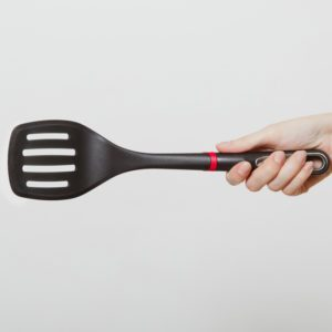 Close up of female hand horizontal holding black spatula isolated on white background.
