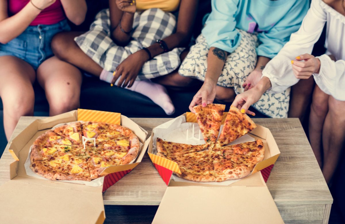 Diverse women sitting on the couch eating pizza together