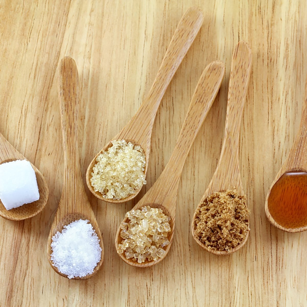 Spoons of different types of sugar, sugar cube, granulated white sugar, granulated light brown sugar, brown sugar crystals, soften brown sugar, honey on the wooden background