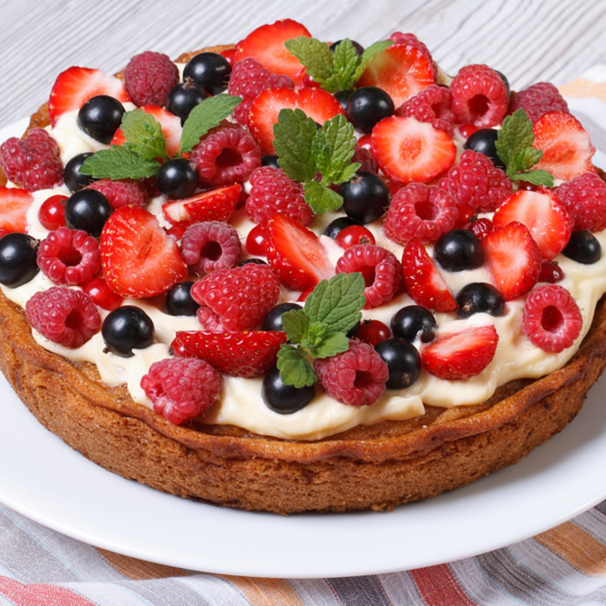 berry tart with fresh strawberries, raspberries, currants, mint and cream close up on the table