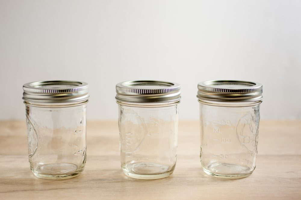Empty canning jars await use on a wooden table