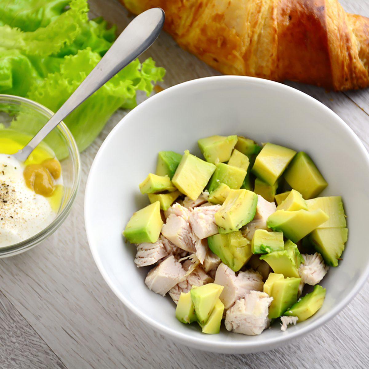 Preparing chicken avocado salad with light yogurt dressing on gray wooden table.