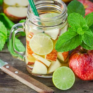 Mug delicious refreshing drink of apple fruits with mint on wooden, infused water