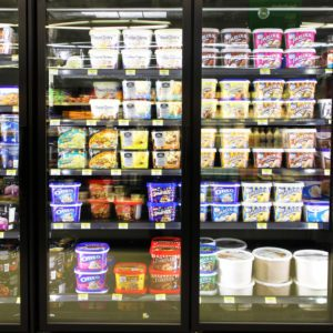 Different brands and flavors of ice cream on fridge shelves in a supermarket. Based on studies, half of the population in North America eat ice cream regularly