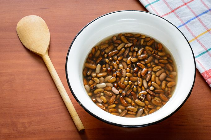 Brown beans soaking in water before to be cooked in a pot for the preparation of a tasty soup.