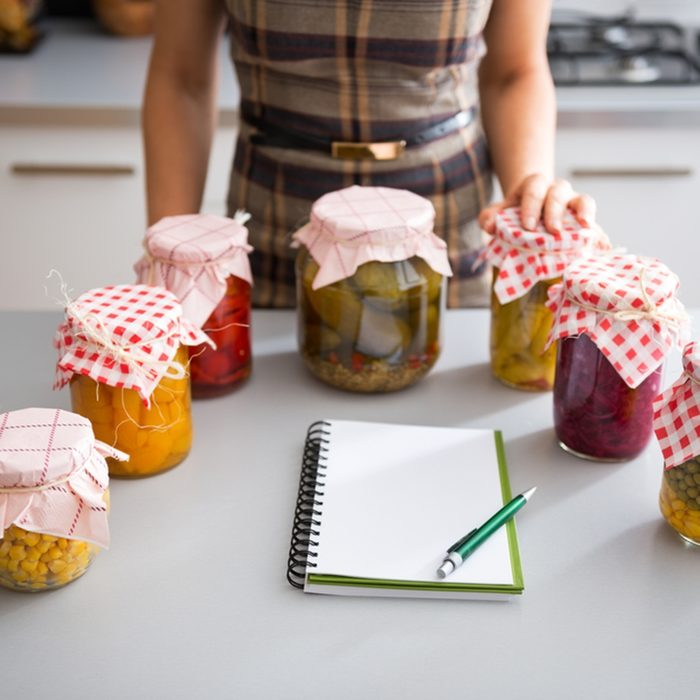 Closeup on notepad and young housewife with jars of pickled vegetables; Shutterstock ID 257211313; Job (TFH, TOH, RD, BNB, CWM, CM): Taste of Home
