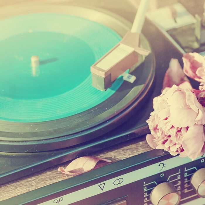 Old vintage good looking turntable playing a track with vinyl and flowers