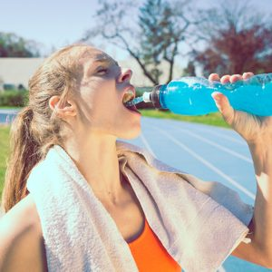 woman drinking sports drink after workout