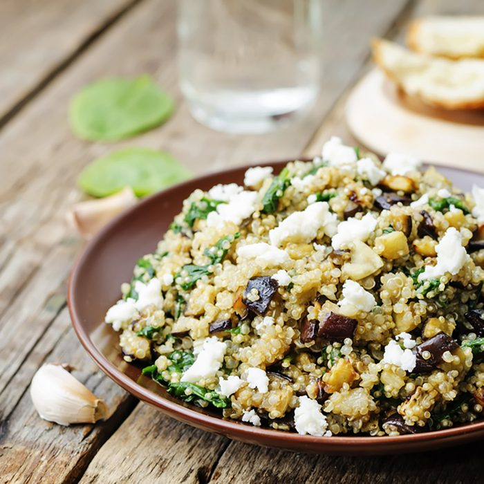 quinoa spinach eggplant feta salad on a dark wood background.