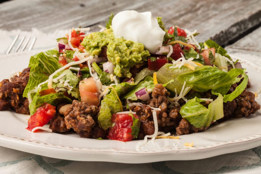 Taco salad on an antique platter on a weathered barn wood table freshly made